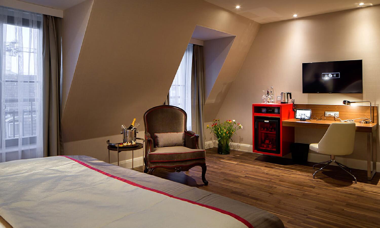 ダークブラウンのフローリングと温かみのあるインテリアが特徴的な、クラシックな208の客室